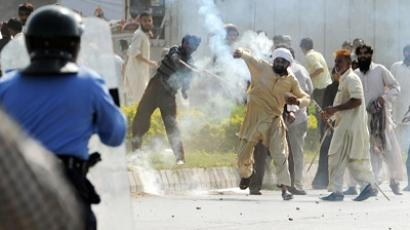 A Pakistani demonstrator throws a tear gas shell towards riot police during a protest against an anti-Islam film in Islamabad on September 21, 2012 (AFP Photo/Aamir Qureshi)
