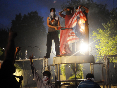 Pakistani Shiite Muslims torch a US flag in front of the US consulate building during a protest against an anti-Islam movie in Lahore on September 17, 2012 (AFP Photo / Arif Ali)