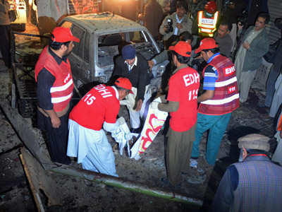 Pakistani rescues collect evidence at the suicide attack site in Peshawar on December 22, 2012. (AFP Photo/A Majeed)