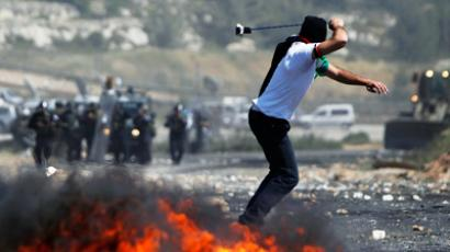A Palestinian protester uses a sling to hurl stones at Israeli troops during clashes outside Ofer prison near the West Bank city of Ramallah May 15, 2012 (Reuters/Darren Whiteside)