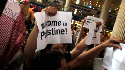 Pro-Palestinian Israeli activists hold signs during a protest at Ben Gurion International Airport (Reuters / Ronen Zvulun)