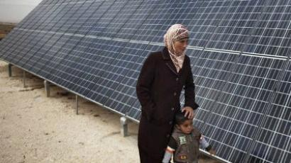 A Palestinian woman and her child walk next to a solar panel in the southern West Bank village of Imneizil on November 16, 2011. (AFP Photo / Menahem Kahana)