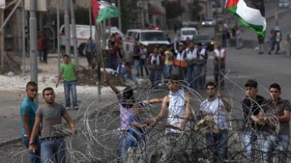 Qalandia: Palestinian youths try to remove barbed wire during clashes with Israeli forces at the Qalandia checkpoint between Jerusalem and Ramallah on September 23, 2011. (AFP Photo/Menahem Kahana)