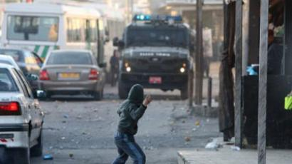 A masked Palestinian youth throws stones towards Israeli border guards during clashes on December 1, 2011 in the east Jerusalem refugee camp of Shuafat (AFP Photo / AHMAD GHARABLI)
