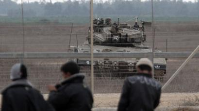 An Israeli army tank keeps position near a security fence standing on the Gaza border with Israel, east of Khan Yunis, in the southern Gaza Strip, during a demonstration by Palestinian youths on November 23, 2012..(AFP Photo / Said Khatib)