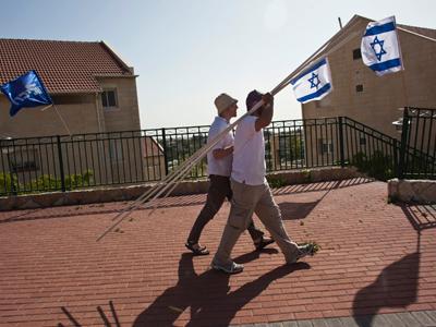 Men walk near Israeli flags in Ulpana, on the edge of the West Bank Jewish settlement of Beit El, north of Ramallah (Reuters/Nir Elias)