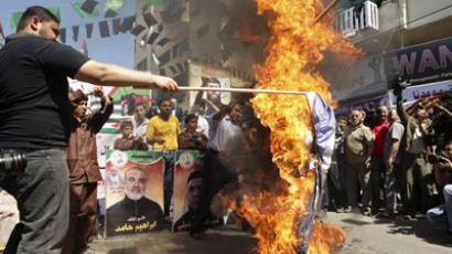 Palestinians burn Israel's national flag during a rally in front of the Red Cross headquarters in Gaza City marking Palestinian Prisoners Day April 17, 2012. (Reuters / Suhaib Salem)