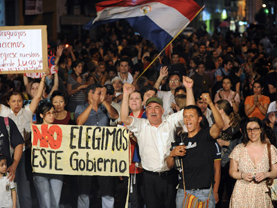 Supporters of Paraguayan former president Fernando Lugo demonstrate against his impeachment and dismissal over 10 days ago in front of the Paraguayan state-owned TV channel's headquarters in Asuncion on July 2, 2012. (AFP Photo/Norberto Duarte)