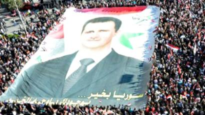 Syria, Damascus: Syrians wave their national flag and hold up a huge banner of Syrian President Bashar al-Assad as they rally in central in Damascus on November 20, 2011. (AFP Photo / Louai Beshara)