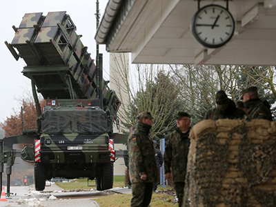 Soldiers of the Air Defence Missile Squadron 2 stand guard with Patriot missile launchers in the background in Bad Suelze, northern Germany  on December 4, 2012. (AFP Photo / Bernd Wustneck)