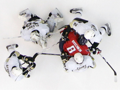 Alex Ovechkin  is surrounded by Pittsburgh Penguins (AFP Photo /  Bruce Bennett)