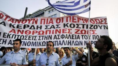 A protestor holds a Greek flag by demonstrating policemen by the Greek parliament in Athens during the rally by police, coast guards and firemen against the new austerity package on June 23, 2011 (AFP Photo / Louisa Gouliamaki)