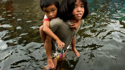 A girl hold a boy on her back to help him cross the floodwaters in a street in Valenzuela, on the outskirt of Manila on August 13, 2012 (AFP Photo / Nicolas Asfouri)