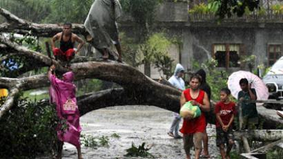 Residents saw an uprooted tree to clear the road after Typhoon Bopha hit Tagum City, southern Philippines December 4, 2012 (Reutrers / Stringer Philippines)