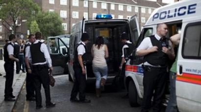 Police officers detaining a woman, center, and loading her into a police van during a routine stop and search operation on Wednesday, Aug. 10, 2011 in Camden, North London (AFP Photo / Getty Images)