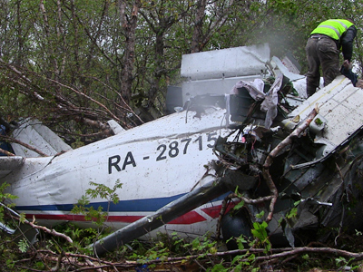 Policemen examining the AN-28 plane downfall site (RIA Novosti)