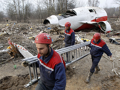 Workers carry a ladder at the site of a Polish government Tupolev Tu-154 aircraft crash in Smolensk. (Reuters / Sergei Karpukhin)