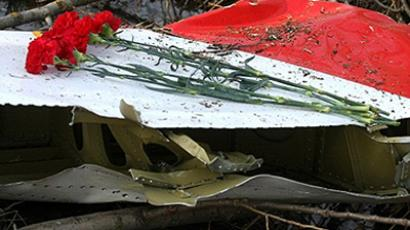 Smolensk: Flowers lay on the wreckage of crashed Polish government Tupolev Tu-154 aircraft near Smolensk airport on April 11, 2010 (AFP Photo / Andrey Smirnov)