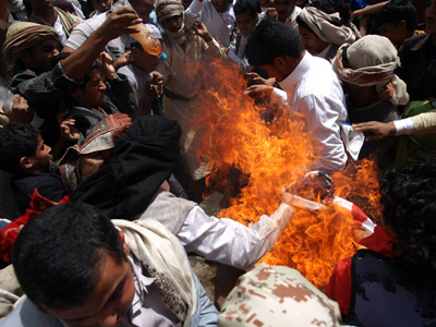 Yemeni protesters burn a US flag during a demonstration at a street leading to the US embassy in Sanaa on September 14, 2012 against a film mocking Islam. (AFP Photo/Mohammed Huwais)