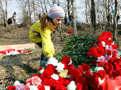 Russia, Smolensk : A girl lays flowers on the wreckage of crashed Polish government aircraft on April 11, 2010 (AFP Photo / Andrey Smirnov)