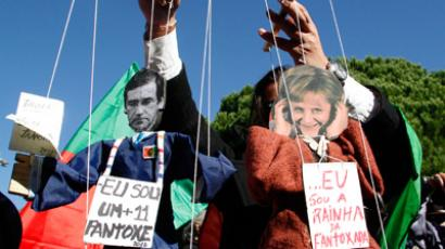 A protester plays with puppets representing Portugal's Prime Minister Pedro Passos Coelho (L) and Germany's Chancellor Angela Merkel in front of the presidential palace ahead of Merkel's arrival in Lisbon November 12, 2012 (Reuters / Hugo Correia)
