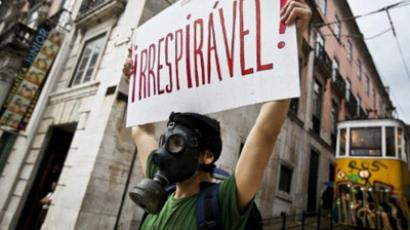 "Portugal, Lisbon: A man wears an oxygen mask and holds a poster that reads ""unbreathable"" as a form of protest, portuguese and spanish youths protest in downtown Lisbon on May 28, 2011, they protest against the economic crises and sky-high jobless rate in their countries. (AFP Photo / Patricia De Melo Moreira)"