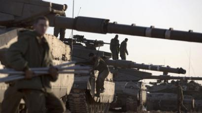 Israeli soldiers prepare tanks at an Israeli army deployment area near the Israel-Gaza Strip border, in preparation for a ground operation in the Palestinian coastal enclave on November 18, 2012. (AFP Photo/Menahem Kahana)