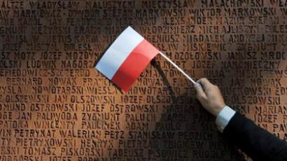 A person waves a Polish flag at the Monument dedicated to Polish officers, murdered in the 1940 Soviet-era Katyn massacre (AFP Photo/ Sergei Supinsky)