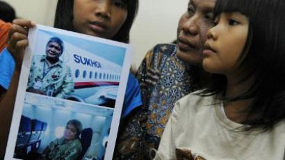 Indonesian mother displays a photograph of her missing husbandi, taken aboard the ill fated Russian Sukhoi Superjet 100 (AFP Photo / Romeo Gacad)