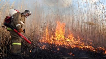 A member of the Greenpeace of Russia puts out fire (RIA Novosti / Anna Baskakova)