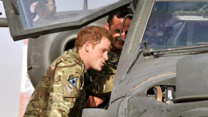 Britain's Prince Harry examines the interior of an Apache helicopter with a member of his 622 Squadron, 3 Regiment Army Air Corps, part of 16 Air Assault Brigade, at Camp Bastion in Helmand Province, Afghanistan (AFP Photo / John Stillwell)