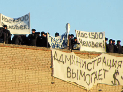 "A picture taken on November 25, 2012, shows a group of inmates standing on a roof of the Prison Number 6 in Kopeisk in the Chelyabinsk region during their a protest which the authorities said was aimed at obtaining the release of convicts from solitary confinement and the easing of conditions. The posters read: ""We are 1,500 human beings!"" (top L-R), ""The [prison's] administration extort money!"" (bottom C). The Russian authorities said today they had quelled a rare uprising at a prison in the Urals region that saw inmates climb on the roof and bloody clashes between police"