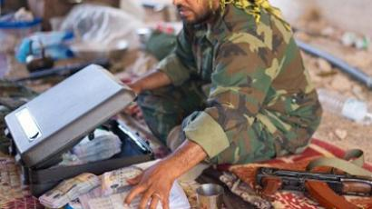A fighter loyal to the National Transitional Council (NTC) sits with a large quantity of money (AFP Photo / Leon Neal)
