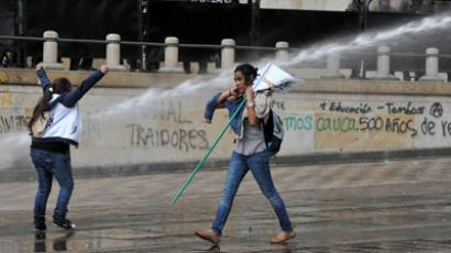 Riot policemen throw water jets at protesters during a march on October 12, 2012, in Bogota.(AFP Photo / Guillermo Legaria)