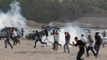 Anti-government protesters run for cover as tear-gas is seen during their attempt to protest at the area where Bahrain's main opposition party Al Wefaq planned to held their anti-government rally in village of Karrana east of Manama, June 15, 2012 (Reuters/Hamad I Mohammed)