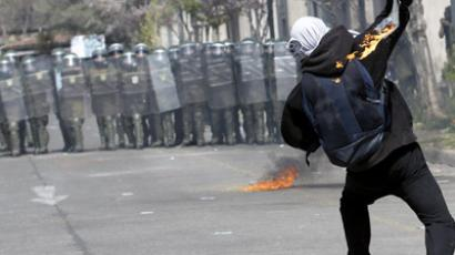 A demonstrator throws a molotov bomb against riot police officers during a protest marking the 1973 military coup, in Santiago September 9, 2012. (Reuters/Ivan Alvarado)