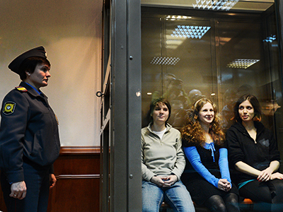 "Members of the all-girl punk band ""Pussy Riot"" (from L)  Maria Alyokhina, Yekaterina Samutsevich and Nadezhda Tolokonnikova sitting in a glass-walled cage in Moscow, on October 10, 2012. (AFP Photo / Natalia Kolesnikova)"