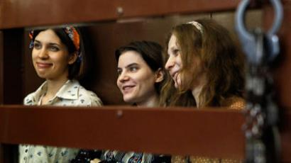"Nadezhda Tolokonnikova (L), Yekaterina Samutsevich and Maria Alyokhina (R), members of female punk band ""Pussy Riot"", attend their trial inside the defendents' cell in a court in Moscow.(Reuters / Maxim Shemetov)"
