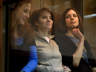 "Members of the all-girl punk band ""Pussy Riot"" (L-R) Yekaterina Samutsevich, Maria Alyokhina and Nadezhda Tolokonnikova sit in a glass-walled cage in Moscow, on October 1, 2012. (AFP Photo/Natalia Kolesnikova)"