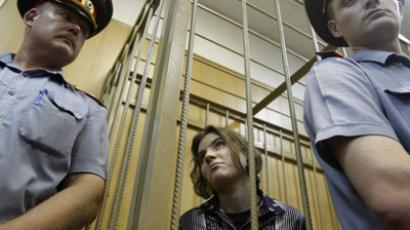 "Yekaterina Samutsevich (C), a member of female punk band, ""Pussy Riot"", looks out from a cage during a court hearing in Moscow July 4, 2012. (Reuters/Sergei Karpukhin)"