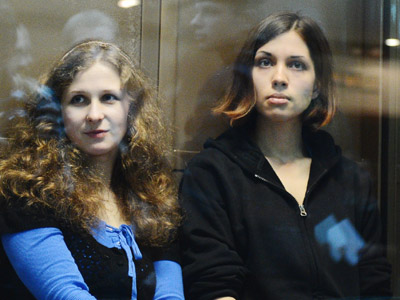 "A picture taken on October 10, 2012, shows two jailed members of the all-girl punk band ""Pussy Riot,"" (L-R) Maria Alyokhina and Nadezhda Tolokonnikova, sitting in a glass-walled cage in a court in Moscow. (AFP Photo/Natalia Kolesnikova)"