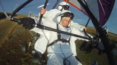 "Russian President Vladimir Putin (foreground) takes part in a scientific experiment as part of the ""Flight of Hope"", which aims to preserve a rare species of cranes, by showing the nursery-reared birds their flying route. At the helm of a motorized hang glider that the birds have taken as their leader, Putin made three flights - the first to get familiar and two others with the birds.(RIA Novosti / Alexsey Druginyn)"