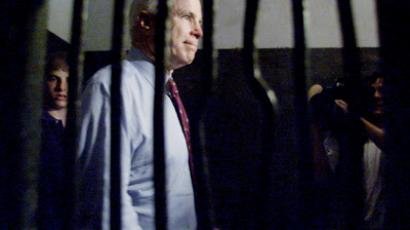 "Vietnam war veteran and former Republican presidential frontrunner, Senator John McCain of Arizona walks past the iron bars of a jail cell within the infamous ""Hanoi Hilton"" jail April 26 on a tour of the former prison in which he spent time as a prisoner of war (Reuters / Jason Reed)"