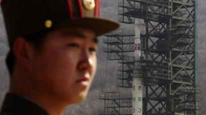 A soldier stands guard in front of the Unha-3 (Milky Way 3) rocket sitting on a launch pad at the West Sea Satellite Launch Site in the northwest of Pyongyang April 8, 2012. (Reuters / Bobby Yip).Video by AP