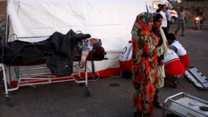 Iranian women stand near an injured woman resting next to a makeshift clinic set up by Red Crescent aid workers in the town of Varzaqan some 60 kms northeast of Tabriz (AFP Photo / Hamed Nazari)