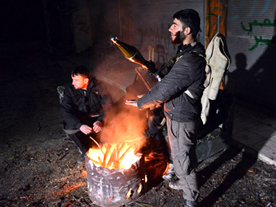 Syrian rebels warm themselves at a security check point in Bdama, northwest of Jisr al-Shughur in the Idlib province, late 22 January, 2013. (AFP Photo / Aamir Qureshi)