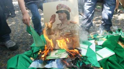 A portrait of Libyan leader Mummar Gaddafi and copies of his Green Book are set on fire by demonstrators during a protest outside the Libyan embassy in Ankara (AFP Photo / Adem Altan)