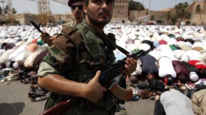 Tripoli: Libyan NTC fighters stand guard as as people perform the weekly Friday noon prayer at the Martyrs' Square -- called Green Square under Moamer Kadhafi -- in Tripoli on September 2, 2011 as the new leaders won massive international support for their plans to rebuild the war-shattered country. (AFP Photo / Patrick Baz)