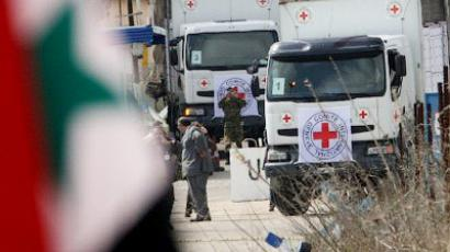 A Syrian flag flies in front of International Red Cross Committee trucks (AFP Photo / Louai Beshara)