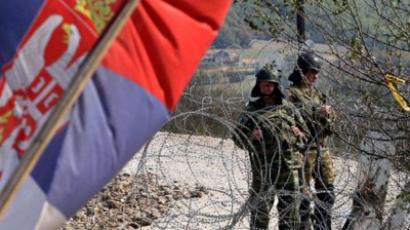 A Serbian flag is seen as the NATO Kosovo Force (KFOR) soldiers stand guard on a barricade at the border crossing Jarinje between Serbia and northern Kosovo on September 28, 2011. (AFP Photo / Sasa Djordjevic)